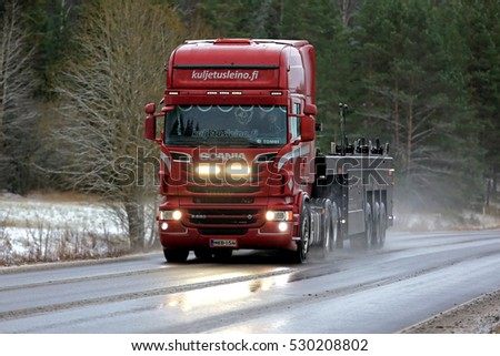 SALO, FINLAND - DECEMBER 2, 2016: Red Scania R560 V8 truck of Kuljetus Pertti J. Leino Oy on wet road with road salt in snowfall. The driver flashes the high beam lights briefly.