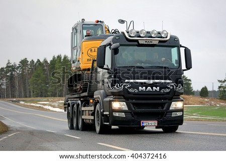 SALO, FINLAND - JANUARY 30, 2016:  MAN TGS 35.540 Truck hauls New Holland Kobelco Excavator along road in South of Finland. The TGS is designed for heavy-duty and distribution transport. - stock photo