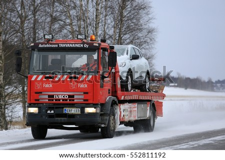 SALO, FINLAND - JANUARY 7, 2017: Red Iveco tow truck tows a car along road on a cold day in winter. The subzero temperatures can cause many mechanical failures of motor vehicles.