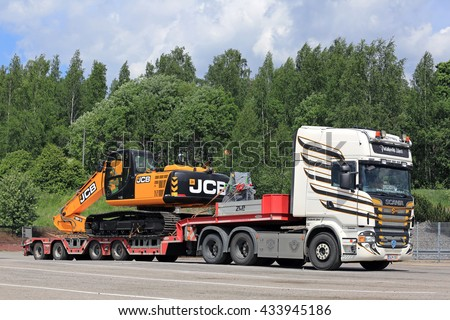 SALO, FINLAND - JUNE 3, 2016: Colorful customized Scania R560 transports JCB JS 210 LC Hydraulic Excavator on lowboy trailer.  - stock photo