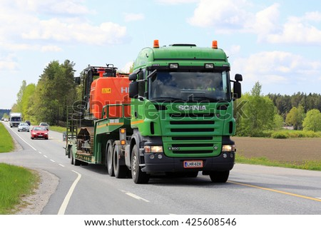 SALO, FINLAND - MAY 20, 2016: Green Scania R500 semi truck transports Hitachi crawler excavator along rural spring highway in South of Finland. - stock photo
