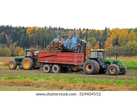 SALO, FINLAND - OCTOBER 4, 2015: Unnamed farmer harvests sugar beet with John Deere 3050 tractor and Edenhall 722 harvester. The Finnish season of sugar beet harvest begins in October. - stock photo