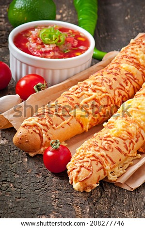 Salsa dip in bowl of bread and cheese sticks on wooden background - stock photo