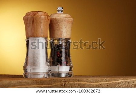 Salt and pepper mills on yellow