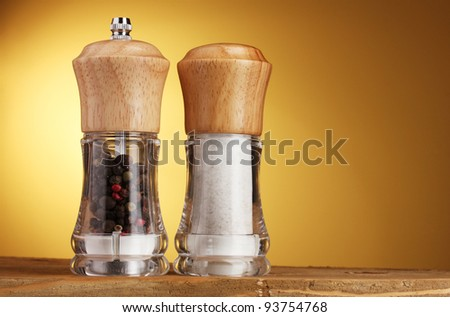 Salt and pepper mills on yellow - stock photo