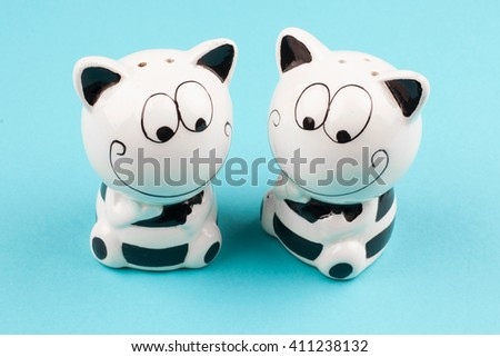 Salt and pepper. Seasoning to the dishes. Funny tableware. The salt and pepper in the shape of cats on a blue background - stock photo
