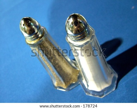 Salt and Pepper shakers against blue tablecloth - stock photo