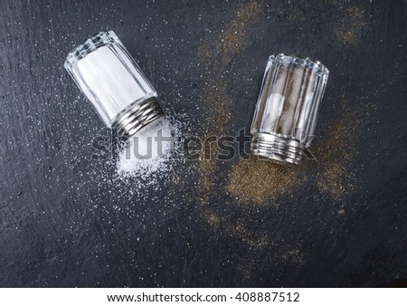 Salt and Pepper Shakers on a slate slab (selective focus; close-up shot) - stock photo