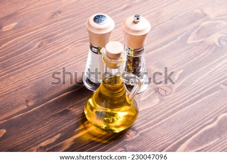 salt and pepper, sunflower oil on brown table top and side views - stock photo