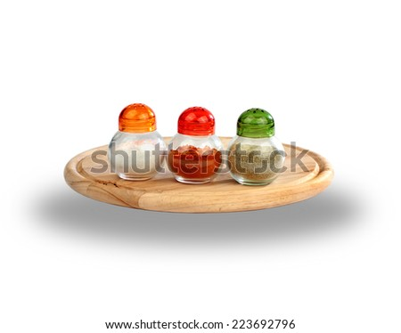 Salt, black pepper, paprika boxes on wooden cutting plate over white background - stock photo