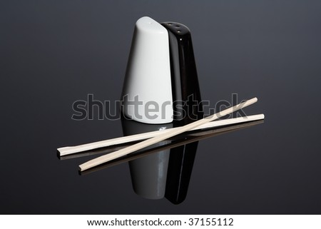 Salt-cellar and pepper-box and chopsticks on mirror surface - stock photo