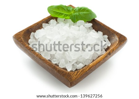 Salt crystals in wooden bowl and basil leaf closeup - stock photo