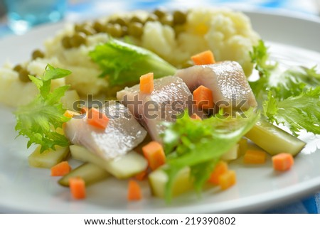 Salt herring with mashed potato and vegetables. Selective focus on the fish - stock photo