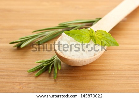 salt in spoon with fresh  rosemary and basil on wooden background