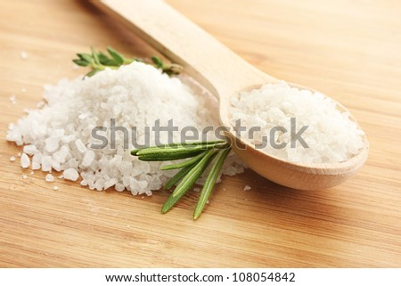 salt in spoon with fresh  rosemary and thyme on wooden background - stock photo