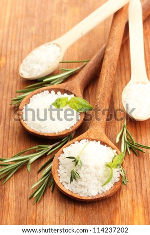 salt in spoons with fresh basil, thyme and rosemary isolated on white