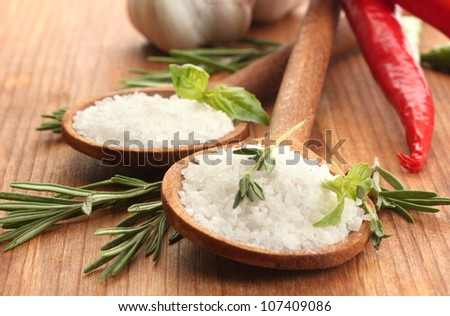 salt in spoons with herbs and vegetables isolated on white