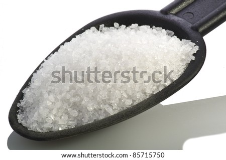 salt in the black spoon on white - stock photo