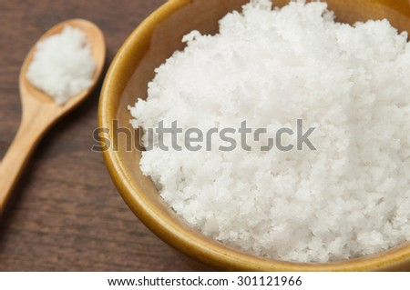 salt in wood spoon on wooden background .