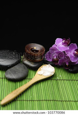 salt in wooden spoon with candle and orchid on green mat