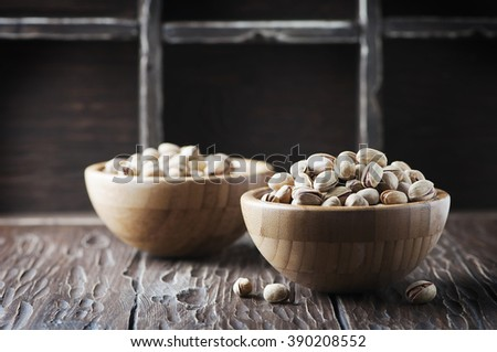 Salt pistachio nuts in the wooden bowl, selective focus - stock photo