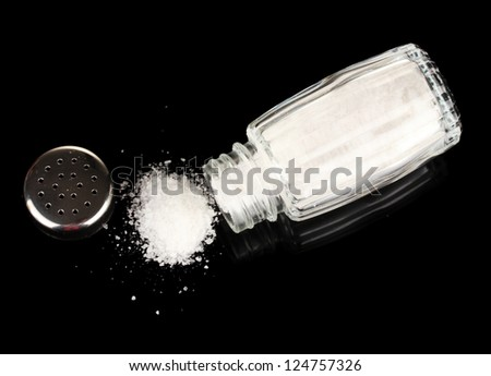 Salt shaker with spilled salt isolated on black - stock photo