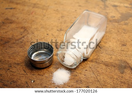 Salt shaker with unscrewed cap with salt spilled on table - stock photo
