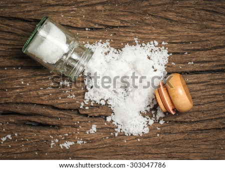 salt sprinkled on wooden table - stock photo