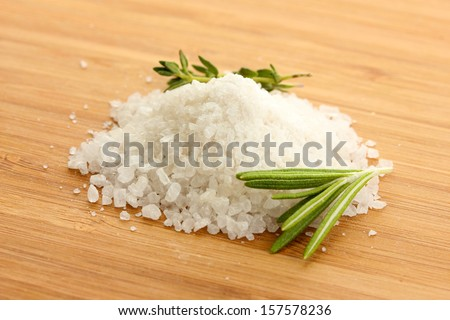 salt with fresh rosemary and and thyme on wooden background - stock photo