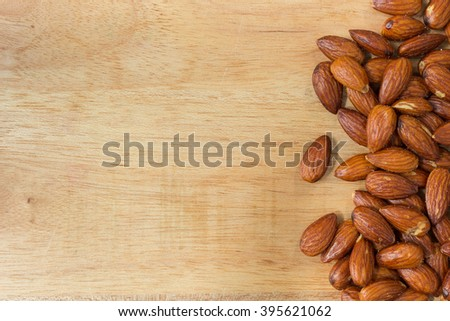 Salted almond nuts on wood board on right hand side, leaving space for text - stock photo