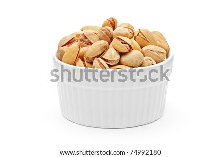 Salted and roasted pistachio nuts in a porcelain bowl isolated on white background - stock photo