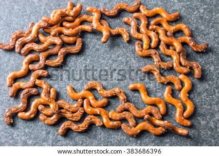 Salted Baked Pretzel Sticks on Dark Rustic Table. - stock photo
