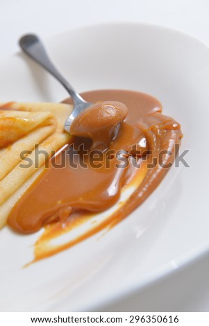 salted caramel and pancakes on a white plate - stock photo