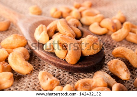 Salted cashew nuts on ladle. Selective focus on the cashew nuts in ladle  - stock photo