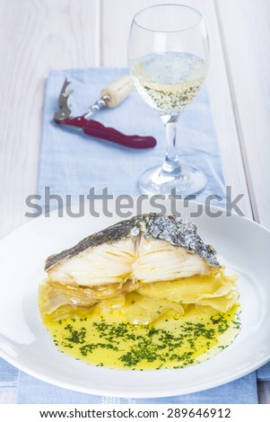 Salted cod fish oven baked with potatoes onion and olive oil - stock photo