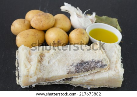 salted cod fish with potato, oil and garlic - stock photo