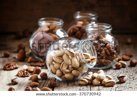 Salted pistachios in a glass jar, nut mix, selective focus - stock photo