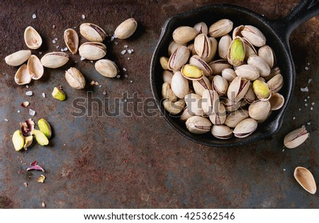 Salted roasted pistachios nuts with shell and salt  in  in black small cast-iron pan over old rusty iron textured background. Top view. With copy space