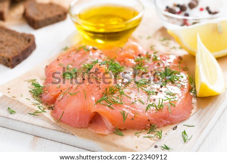 salted salmon, bread and ingredients on a wooden board, close-up, horizontal - stock photo