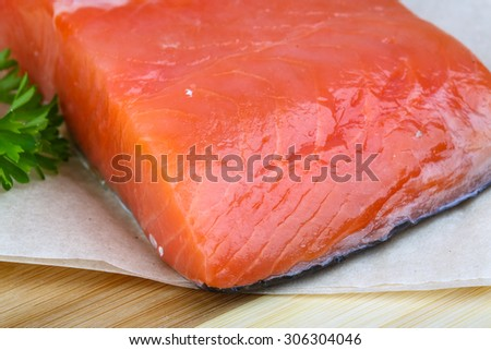 Salted salmon fillet with parsley leaf on the wood background
