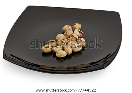 Salted shelled roasted pistachios on a black plate. - stock photo