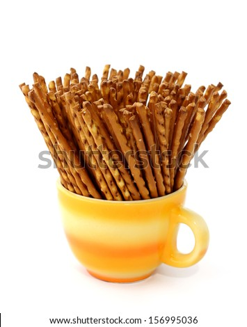 salted sticks in yellow cup isolated on white background - stock photo