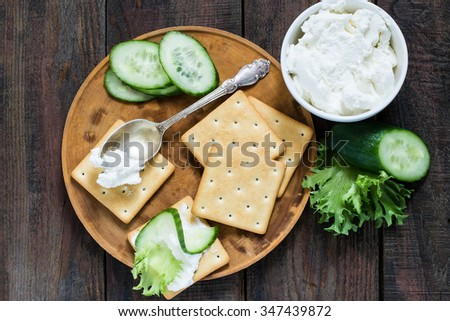 Saltine crackers on a wooden board, lettuce, cucumber and ricotta in a jar topped with a spoon on a cracker - stock photo