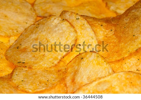 salty and spiced potato fries crisps on background, shallow DOF