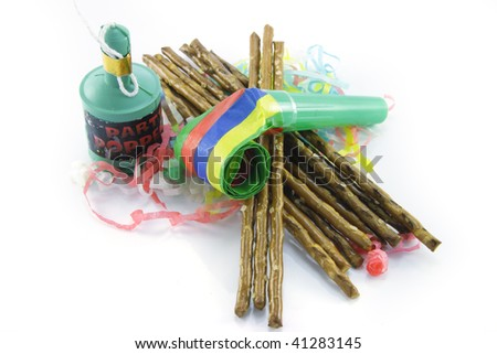 Salty brown tasty pretzels and party blower with party popper and streamers on a reflective white background - stock photo