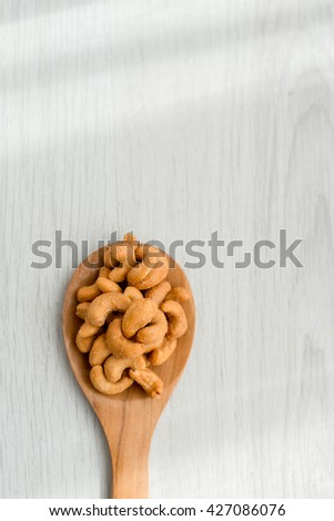 Salty cashew nuts in wood spoon on gray wooden table