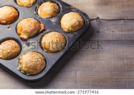 Salty muffins in a baking pan - stock photo