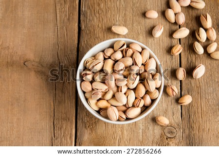 Salty pistachios nuts in bowl on rustic wooden background, close up, horizontal, copy space, vegetarian food - stock photo