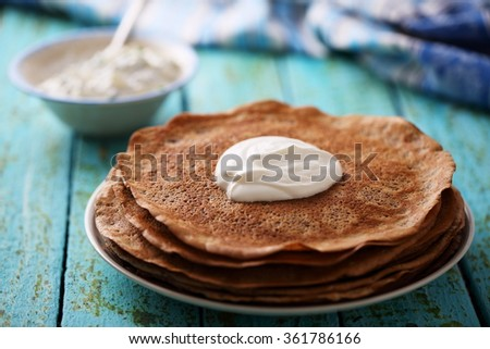 """Salty snack for Shrovetide. Pancakes with chicken liver and sauce """"tartar"""" with marinated cucumber - stock photo"""