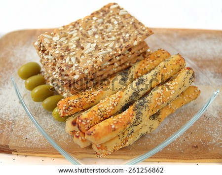 salty sticks with sesame and poppy seeds, Bread sticks or Pretzel sticks,linen tiles and olives - stock photo